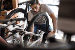 Meccanico che monta una bicicletta nell'officina Fotografie Stock
