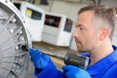 Meccanico che per mezzo dello strumento pneumatico immagini stock libere da diritti