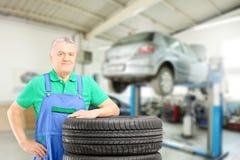 Meccanico che posa sulle gomme davanti all'automobile all'officina riparazioni fotografia stock