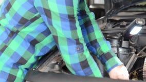 Meccanico che ripara il motore Controllo della cinghia ausiliaria archivi video
