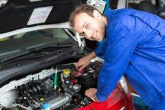 Meccanico che ripara un'automobile in un'officina o in un garage Fotografie Stock Libere da Diritti
