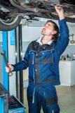 Meccanico che ripara un'automobile sollevata con la grande chiave Fotografia Stock