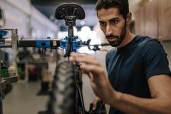 Meccanico che ripara una bicicletta in officina Fotografie Stock