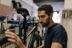 Meccanico che ripara una bicicletta in officina Fotografie Stock Libere da Diritti