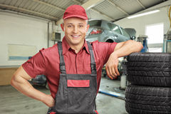 Meccanico che si appoggia una pila di gomme in un garage Fotografia Stock Libera da Diritti