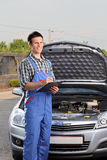Meccanico che si leva in piedi vicino ad un'automobile con il cappuccio aperto Fotografie Stock