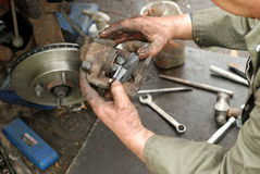 Meccanico che spinge il nuovo rilievo di freno nel vecchio compasso. Immagini Stock