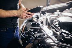 Meccanico che verifica sistema elettrico sull'automobile fotografia stock
