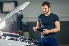 Meccanico che verifica sistema elettrico sull'automobile fotografia stock libera da diritti