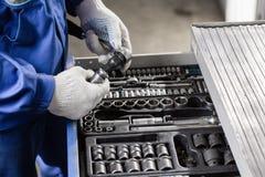 Meccanico con gli attrezzi per la riparazione ed i sistemi diagnostici delle automobili nell'automobile del garage Fotografia Stock Libera da Diritti