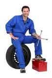 Meccanico con il pneumatico e gli strumenti Fotografia Stock