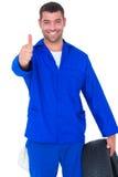 Meccanico con la gomma che gesturing i pollici su Fotografia Stock