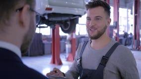 Meccanico con la lavagna per appunti che spiega le spese per la riparazione dell'automobile al suo cliente e che stringe le mani  video d archivio