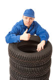 Meccanico con le gomme di automobile sul lavoro Fotografia Stock
