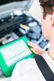 Meccanico con lo strumento diagnostico nell'officina dell'automobile fotografia stock