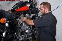 Meccanico del motociclo che lavora al motore americano Immagini Stock