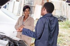 Meccanico della giovane donna e proprietario di automobile al garage Fotografie Stock Libere da Diritti