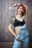 Meccanico della ragazza con arte del fronte che posa con gli attrezzi fotografie stock