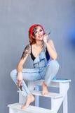 Meccanico della ragazza con arte del fronte che si siede su una scala a libro immagine stock