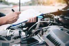 Meccanico di automobile asiatico che fa un rapporto della lista e della nota di controllo sulla lavagna per appunti della carta fotografie stock