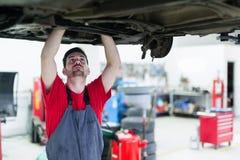 Meccanico di automobile che lavora al centro di servizio automobilistico fotografie stock