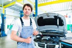 Meccanico di automobile che lavora con lo strumento nell'officina di servizio immagine stock