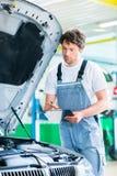Meccanico di automobile che lavora con lo strumento nell'officina di servizio fotografia stock