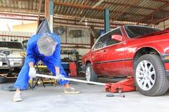 Meccanico di automobile che mette martinetto idraulico sotto l'automobile per la riparazione nel servizio di riparazione automati immagini stock
