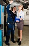 Meccanico di automobile con il cliente femminile Immagini Stock