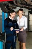 Meccanico di automobile con il cliente femminile Fotografia Stock