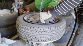 In meccanico di automobile esperto dell'uomo pompa la gomma sulla ruota nell'esterno di servizio di riparazione automatica video d archivio