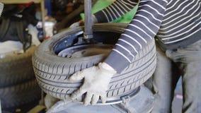 In meccanico di automobile esperto dell'uomo sostituire gomma sulla ruota nell'esterno di servizio di riparazione automatica archivi video