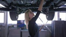 Meccanico di automobile femminile che esamina automobile sollevata al distributore di benzina di riparazione con la compressa in  stock footage