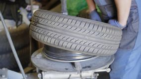 In meccanico esperto dell'uomo mette la gomma sull'automobile spinge dentro il garage di servizio dell'automobile archivi video
