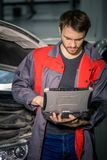 Meccanico Examining Car Engine con aiuto del computer portatile immagini stock libere da diritti