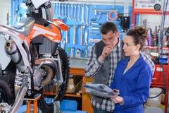 Meccanico femminile della motocicletta che ispeziona bici Fotografie Stock