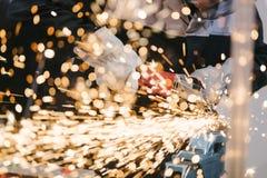 Meccanico in guanti protettivi che tagliano metallo Fotografia Stock