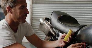 Meccanico maschio che controlla batteria della motocicletta nel garage 4k di riparazione stock footage
