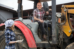 Meccanico maturo dell'agricoltore che posa con i vecchi agrimotors al cortile Fotografia Stock Libera da Diritti