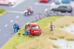 Meccanico miniatura che sostituisce un pneumatico fuori dalla carreggiata Fotografie Stock Libere da Diritti