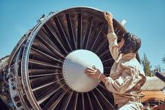 Meccanico nel casco di volo e dell'uniforme che ripara la turbina smantellata dell'aeroplano in un museo all'aperto immagini stock