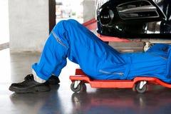 Meccanico nel riposarsi uniforme del blu e nel lavoro sotto l'automobile a aut immagini stock libere da diritti