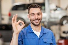 Meccanico o fabbro che mostra okay all'officina dell'automobile Fotografie Stock Libere da Diritti