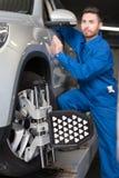 Meccanico piacevole che regola allineamento di ruota dell'automobile Fotografie Stock