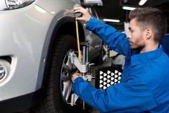 Meccanico professionista che regola allineamento di ruota dell'automobile Fotografia Stock Libera da Diritti
