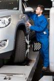Meccanico professionista che regola allineamento di ruota dell'automobile Immagini Stock