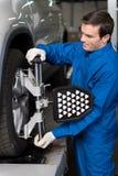 Meccanico professionista che regola il sistema della ruota dell'automobile Fotografie Stock Libere da Diritti