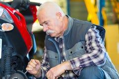 Meccanico senior del motociclo che lavora all'officina immagini stock