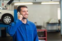 Meccanico sorridente sul telefono Fotografia Stock