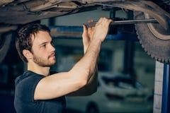 Meccanico sotto l'automobile nella gomma examing del garage e nello stato tecnico immagine stock